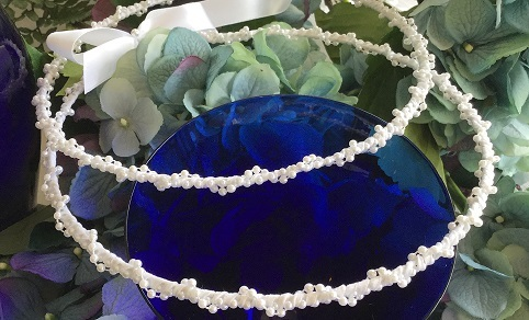 This wedding crown set is made by twogreekwomen.  It has a double wrap of delicate pearls and won't catch in the bride's hair (a big issue for the priest). 