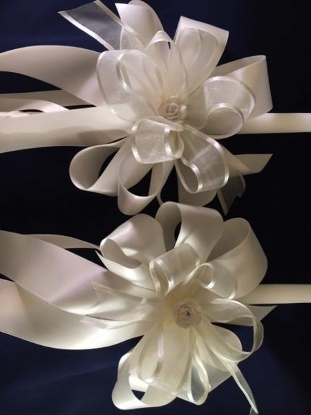 24 inch white candle set with light ivory ribbon, ceramic rose embellishment and a tough of ivory sheet ribbon to catch the church light. 